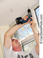 Handyman - Man drilling a hole in a ceiling