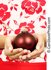 Merry Christmas - A woman holding a christmas ornament on...