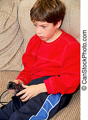 Boy video game - Young boy playing a video game sitting on a...