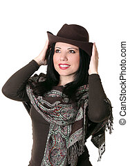Female trying on a brown felt hat - A female trying on...