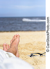 Put you feet up - feet and sandals on the beach with a...