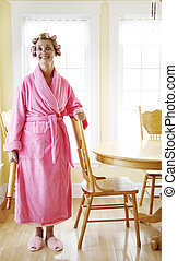 Homemaker - Woman wearing a pink robe and rollers in her...