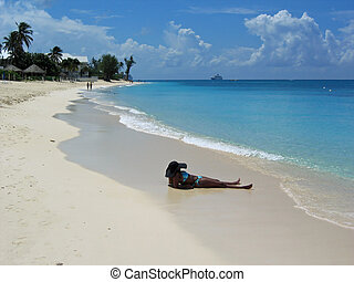 Black Hat at the Beach - An African American woman relaxes...