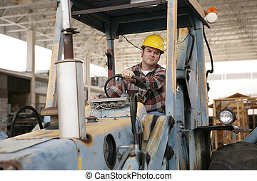 Driving Heavy Equipment - A construction worker driving an...