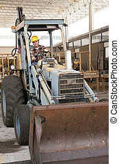 Driving Backhoe - A man on a construction site driving a...
