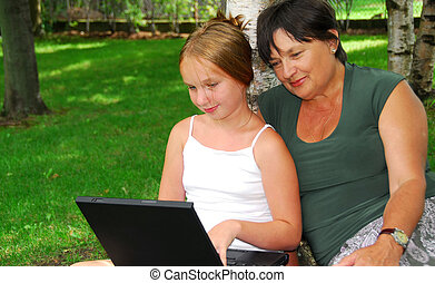 Family computer - Grandmother and granddaughter sitting...