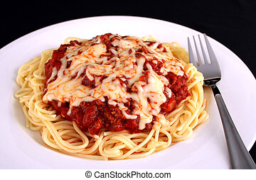 Spaghetti - A plate full of spaghetti with a fork against a...