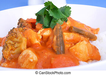 Hot curry - An Indian curry in a white bowl garnished with...