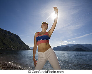 yoga - blond girl doing stretching nearby the lake