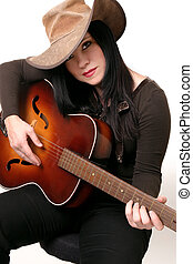 Country western music - A woman sitting on a stool, playing...