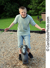 Playground Teen 8 - Teenage boy clowning on a childs ride at...