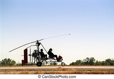Gyrocopter back-lit - A two person gyrocopter, in...