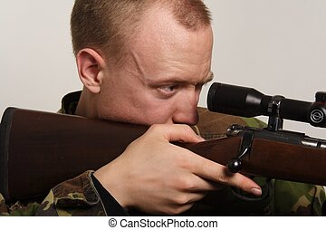 Taking Aim - A young soldier looks through his rifle scope