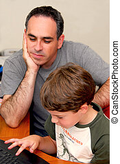 Father son computer - Father teaching his son to work on a...