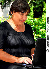 Woman computer - Mature woman working on laptop computer...