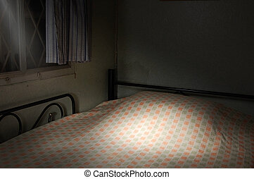 Bed light - A made bed lit from outside at night