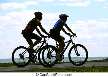 Bicyclists - Two men riding bicycles on sea shore trail,...