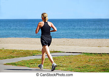Running woman - Young woman joggin by sea side in the summer