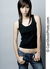 Grungy - A young asian model posing in a studio with grey...
