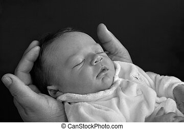 newborn baby - a grandfather hands holding baby