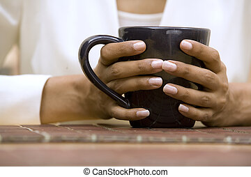 hands holding cup of coffee - hands holding black cup of...