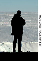 Silhouette of researcher in front of Antarctica - A black...