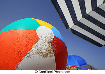 Beach Scene - Beach ball and parasol on busy beach
