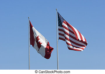Canadian and US flags against a clear blue sky