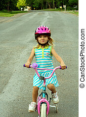 Bike Riding - Little girl riding bike wearing helmet.