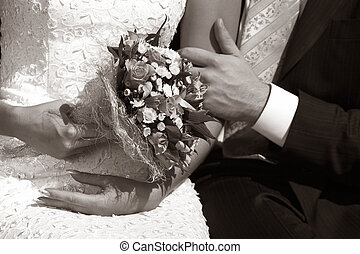 Wedding bouquet in hands of the bride bw+sepia