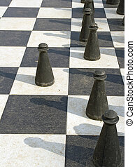 game of chess - a outdoor chessboard with black chess pieces