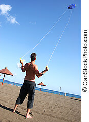 Flying a Kite - Man flying a kite on the beach