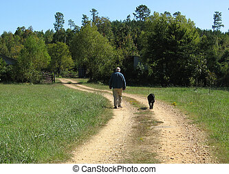 A Man and His Dog - Man and his dog walking down a country...