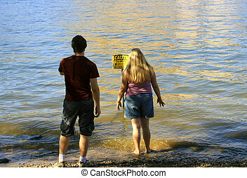 Wading - Attractive young people wading in the water