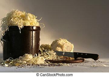 Preparing sauerkraut - Shredded cabbage in the clay jar.