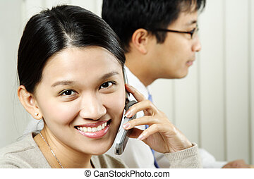 Business team - A businesswoman making a phone call with a...