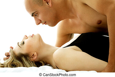 in bed - color image of sweet couple cuddling in bed