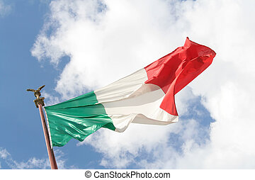 Italian flag from below on cloudy blue sky. The golden eagle...