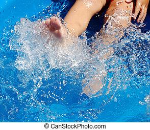 Kicking in Pool - A child kicking water in a blue kiddie...