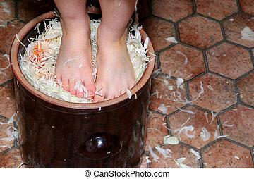 Preparing sauerkraft - Little girl trampling shredded...