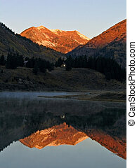 Mountain Reflections - Morning mountain reflection upon a...