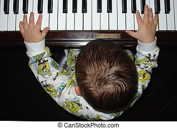 Infant and the piano - Infant playing the piano with both...