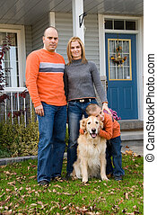 Family - mother, father, son and dog in front of house