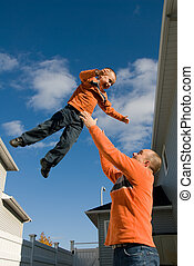 Flying - dad throwing son in the air in backyard