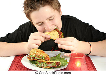 eating tacos - boy enjoying his taco dinner at a Mexican...