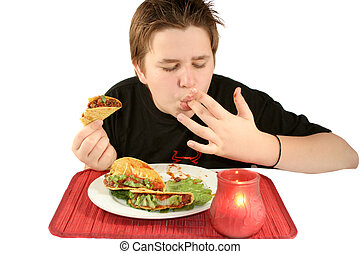 eating tacos - boy licks his fingers while enjoying his taco...