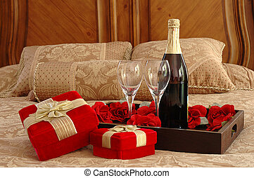 Romantic Surprise - presents, champagne, and roses on a bed