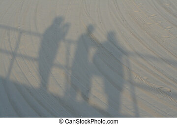 Summer Sand Shadows - Shadow on sand of three individuals...