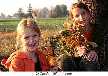 Autumnal walk - Two girls sitting under the tree