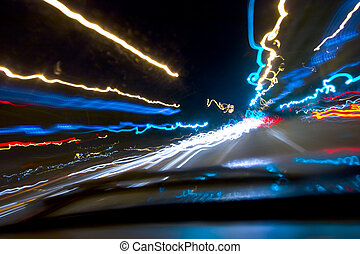 Driving at night - Blurred street lights produced from a...
